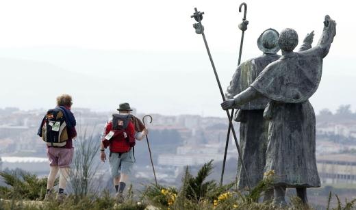 Peregrinos en Santiago de Compostela pasando á beira dunha estatua que representa a peregrinos.