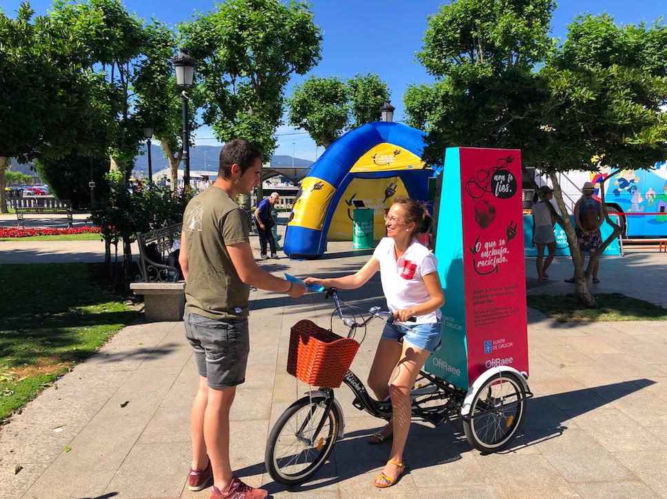 Muller en triciclo repartindo propaganda da campaña.