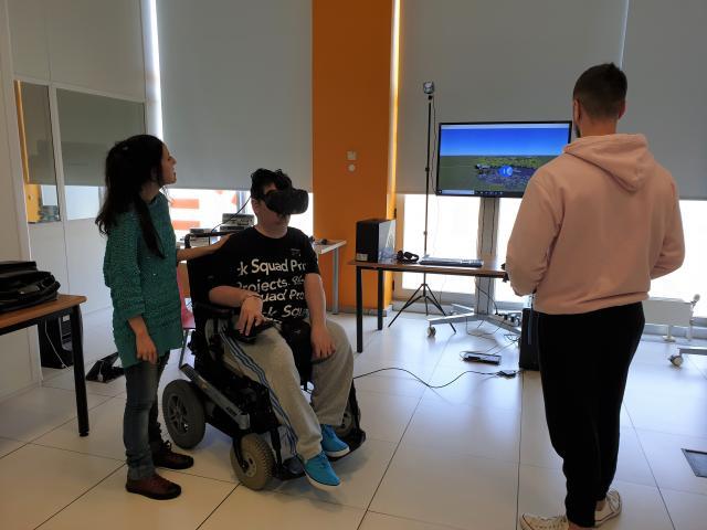 Persoa en cadeira de rodas usando uns cascos de realidade virtual xunto a outras dúas persoas.