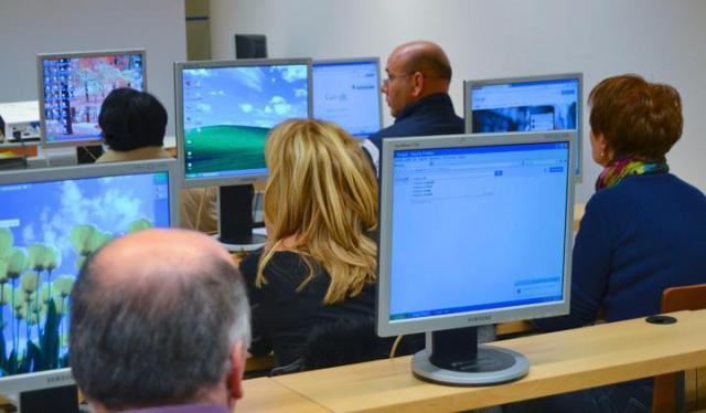 Personas delante de ordenadores asistiendo a un curso informático.