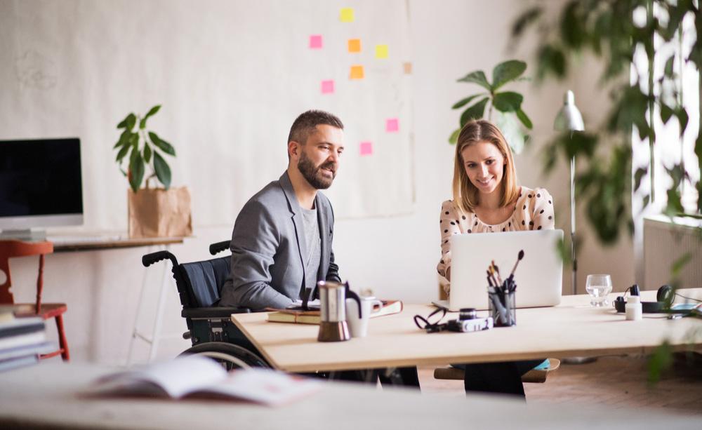 Un home en cadeira de rodas e unha muller traballan nunha oficina.