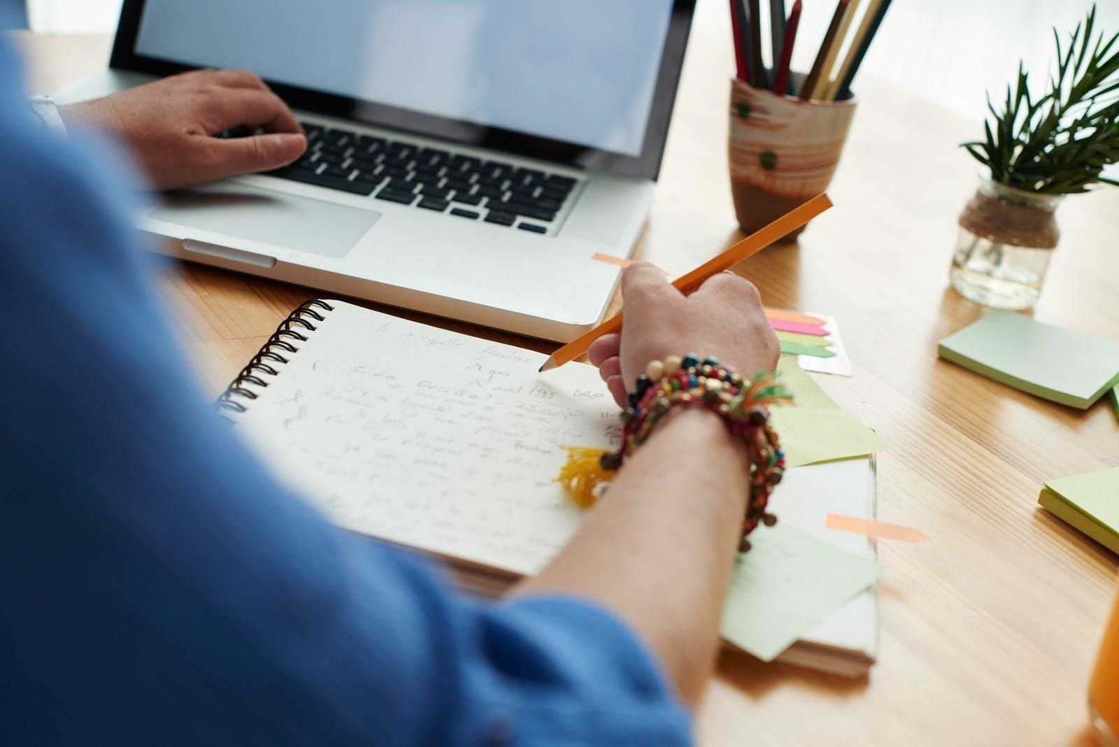 Estudante diante dun portátil e dunha libreta.