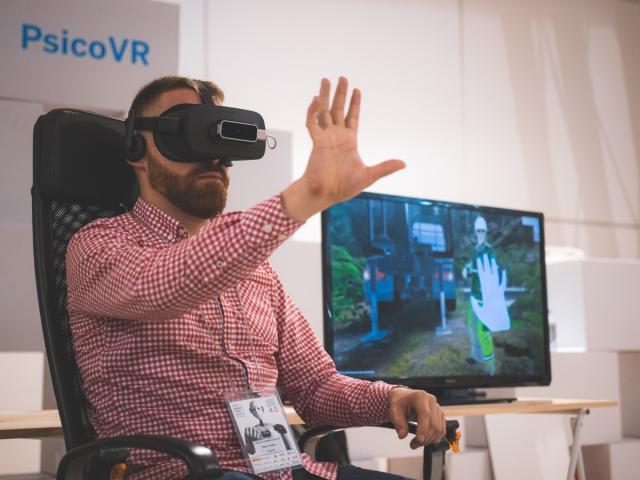 Home sentado usando lentes de realidade virtual.
