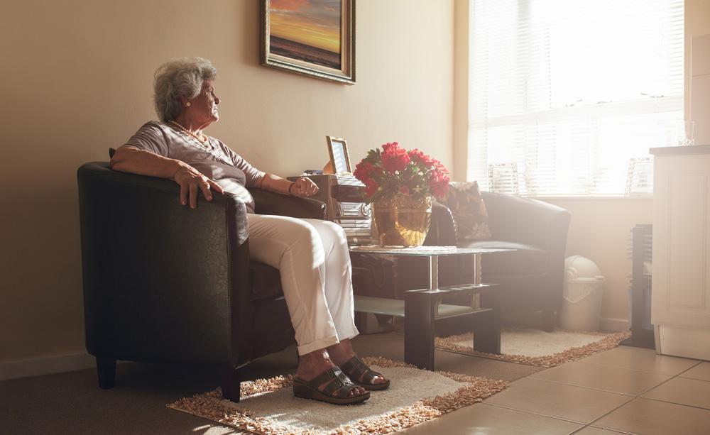 Unha muller maior sentada xunto á xanela no seu fogar.