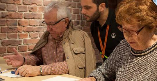Dos personas mayores usando dispositivos móviles asesorados por un joven.