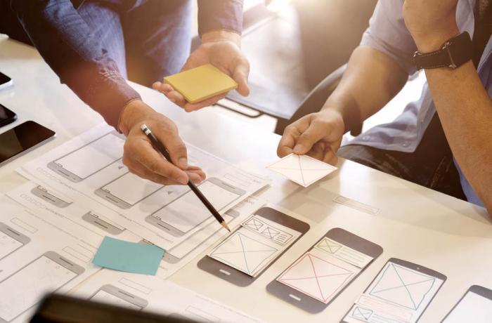 Varias persoas traballan no deseño dunha app para teléfono móbil.