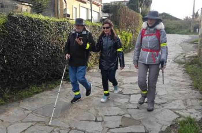 Persoa con discapacidade acompañada doutras dúas, facendo o camiño de Santiago.