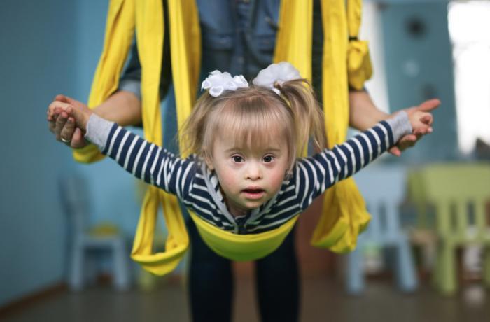 Una niña con síndrome de Down es suspendida en el aire mediante unas cintas.