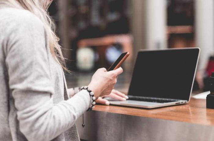 Mujer usando un smartphone y un portátil.