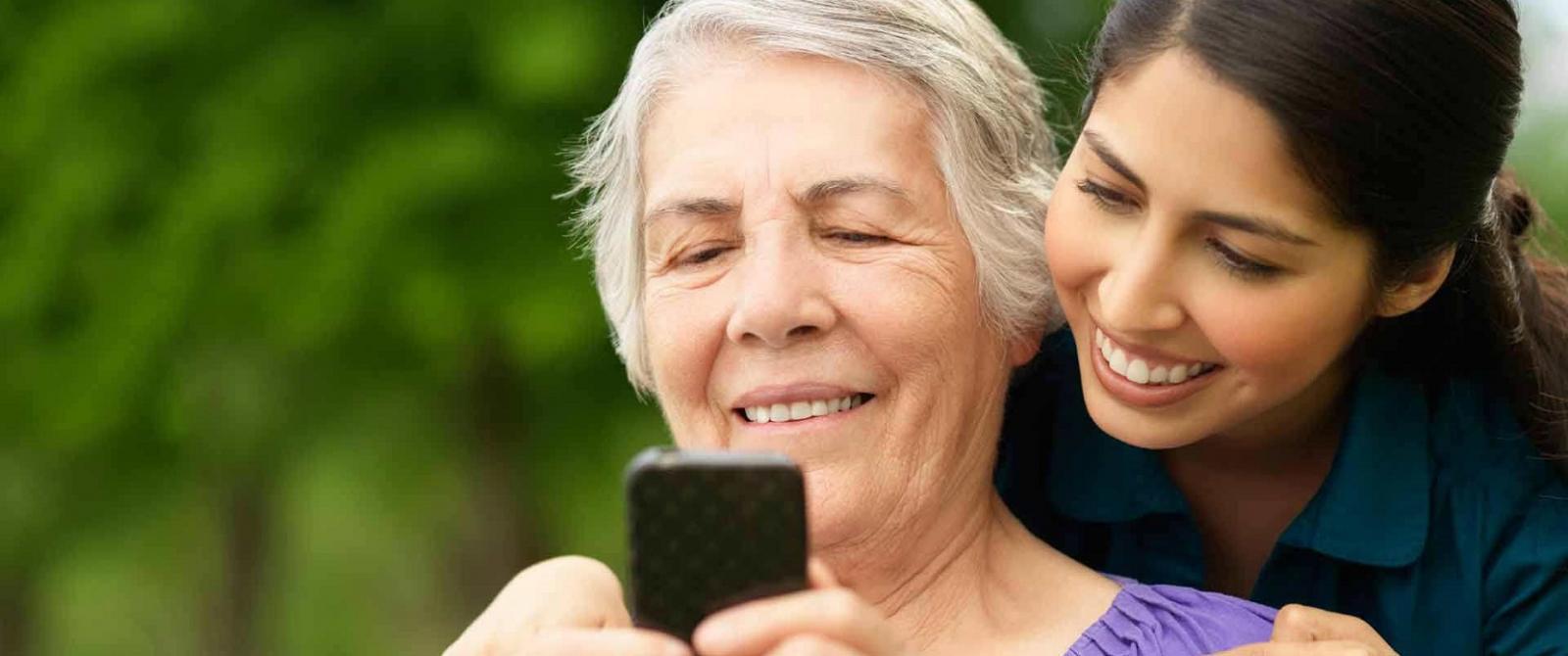 Anciá usando un smartphone e unha rapaza nova detrás dela.