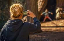 Muller de costas gravando un vídeo cun smartphone.
