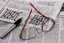 Unhas lentes e un bolígrafo encima dun xornal que mostra crucigramas.