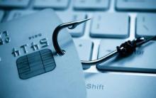 Tarxeta de crédito perforada cun anzol de pesca, encima dun teclado.