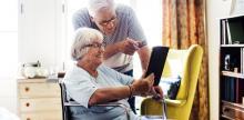 Dúas persoas maiores, unha con discapacidade, mirando unha tablet.