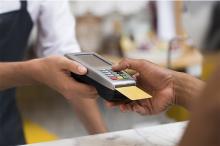 Persoa pagando con tarxeta nunha tenda.
