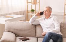 Home de mediana idade falando por teléfono desde un sofá.