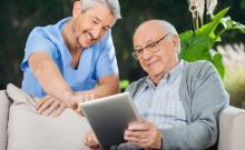 Unha persoa maior utiliza unha tableta xunto a un asistente.