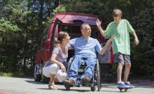 Un hombre en silla de ruedas por una lesión en la médula espinal junto a su mujer y su hijo.