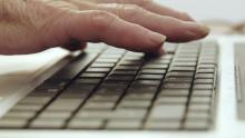 Mans dunha persoa maior sobre un teclado.