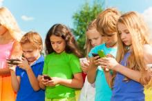 Nenos usando smartphones.