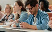 Un mozo utiliza o seu smartphone nunha clase na universidade.