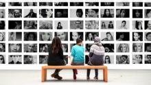 Tres mujeres de espaldas sentadas en un banco mirando fotografías en una pared.