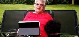 Fotograma do vídeo, cunha muller maior usando unha tablet no seu xardín.