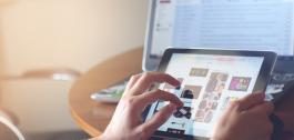 Unha persoa usando unha tableta e un portátil no fogar.