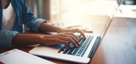 Mans dunha muller sobre o teclado dun portátil.