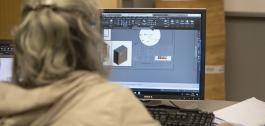 Muller de costas usando un programa de deseño nun ordenador.
