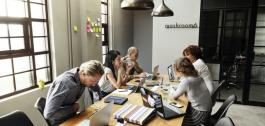 Reunión de empregados nunha mesa con portátiles.