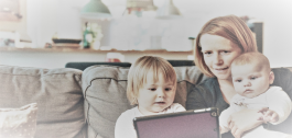 Unha muller con dous nenos pequenos nun sofá mirando unha tableta.